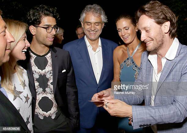Amos Bocelli, Andrea Bocelli, and Veronica Berti watch the Mentalist Lior Suchard perform during an exclusive dinner at the Casa Cavalli estate...