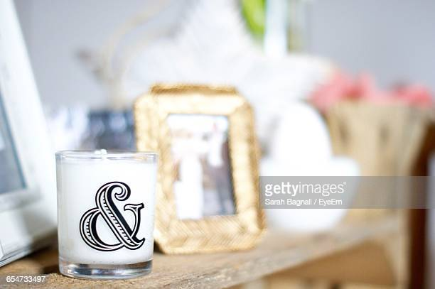 Ampersand Symbol On Tea Light Candle At Table