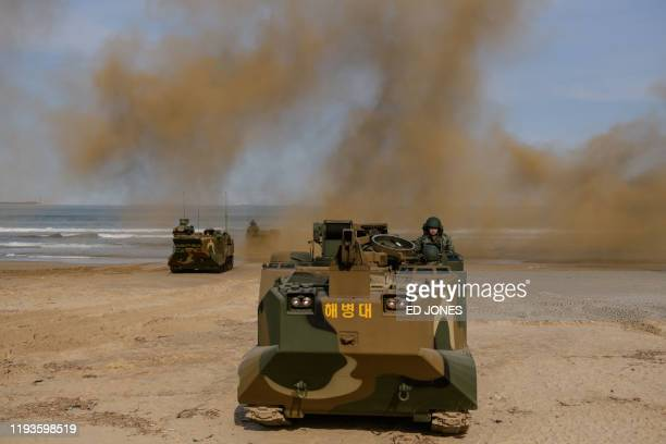 Amphibious armoured personnel carriers perform a demonstration during a training camp for civilian volunteers on a beach near the south-eastern city...