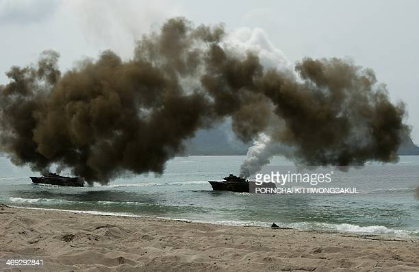 Amphibious attack vehicles power through the water as they participate in an amphibious assault military drill as part of the annual combined...