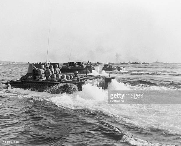 Amphibious tractors loaded with Marines head for the beach at Iwo churning the water into milky foam These craft crawled up the steep beach to put...