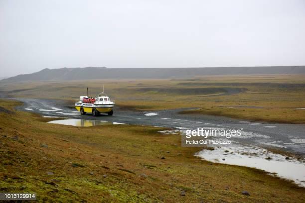 amphibious vehicle and a group of tourists visiting jokulsarlon lagoon, eastern iceland - austurland stock-fotos und bilder