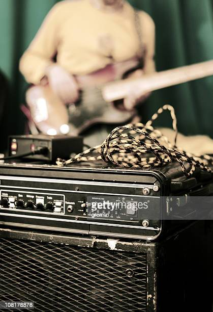 Amplifier and Man Playing Guitar in Background