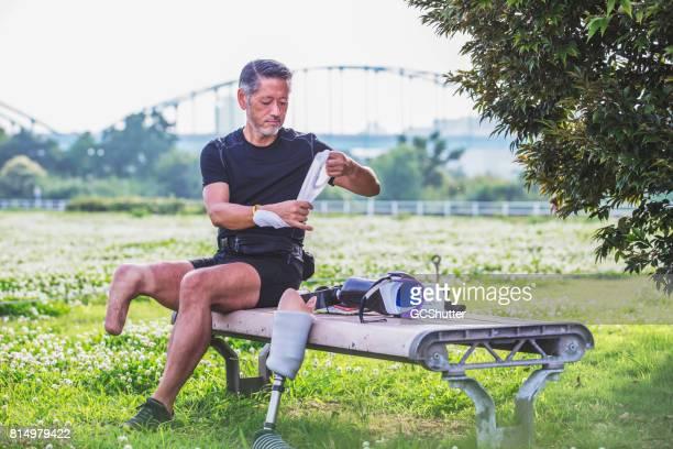 Geamputeerde Japanse man die voorbereiding zelf te veranderen zijn prothetische ledematen