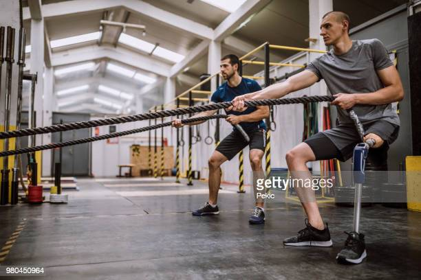 amputee athlete doing battle rope exercises - adaptive athlete stock pictures, royalty-free photos & images
