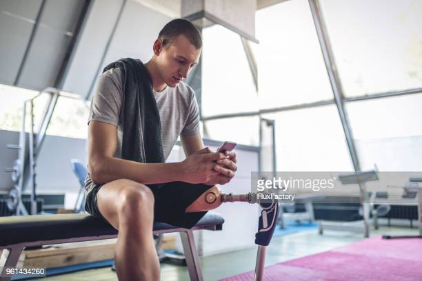 Amputee athlete sitting at the gym texting