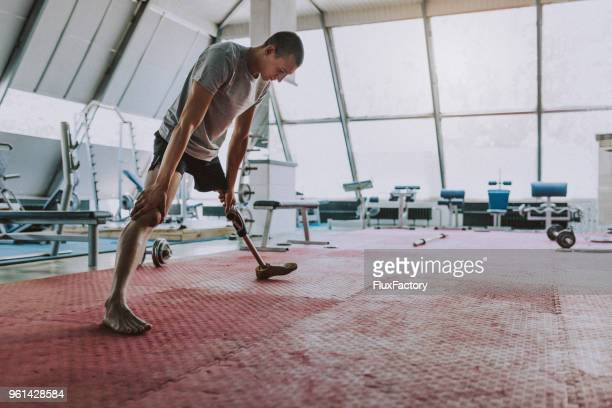 amputee athlete stretching before exercising - artificial limb stock pictures, royalty-free photos & images