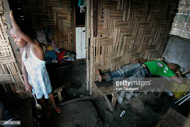 Amputee football MVP player Junior Kulie who is homeless lies on the bench at his friends house in the slum April 29 2008 in Monrovia Liberia...
