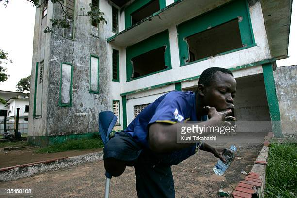 Amputee football player Joseph Kollie who sleeps in an abandoned building brushes his teeth with his finger May 4 2008 in Monrovia Liberia Although...