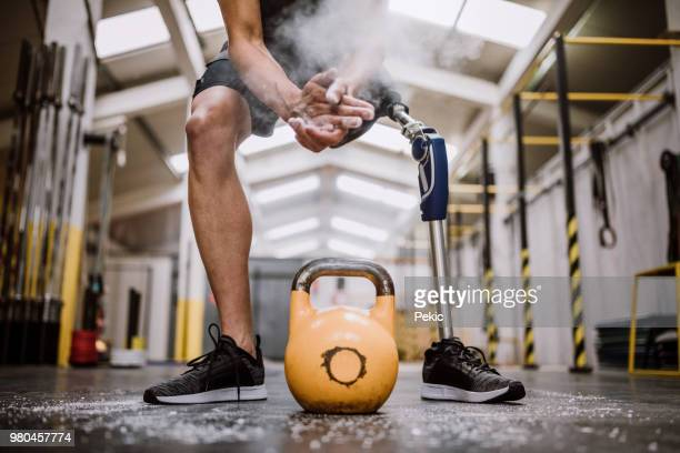 amputee man applying sports chalk so he could lift weights - adaptive athlete stock pictures, royalty-free photos & images