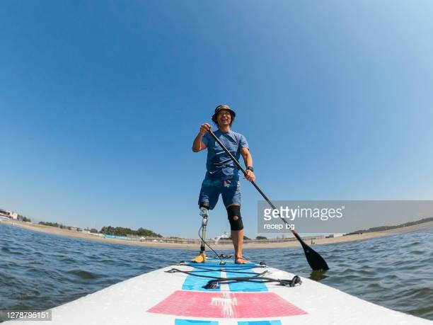 amputee man paddle boarding in sea - active lifestyle stock pictures, royalty-free photos & images