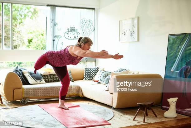 amputee mature woman in leotard practising yoga in sitting room - greater london stock pictures, royalty-free photos & images