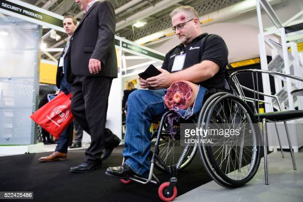 Amputee Ruben Carill of Magnum Services ltd checks his phone as he wears a fake injury during the 'Security and Counter Terror Expo' at the Olympia...