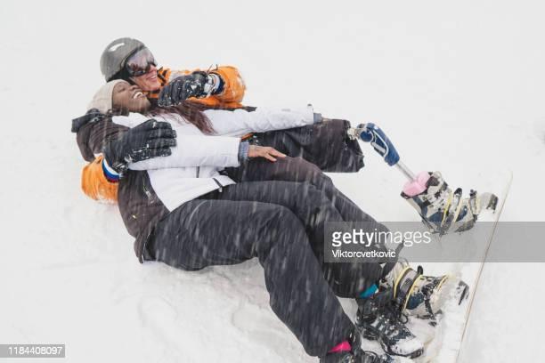 amputierter snowboarder mit afroamerikanerin auf dem schnee - beinamputierte frauen stock-fotos und bilder