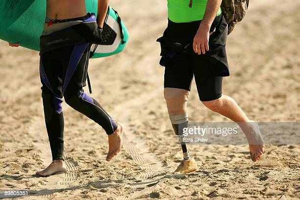 Amputee surfer Ryan West walks down the beach with a local volunteer during Operation Restoration IV on August 14, 2009 in Pismo Beach, California....