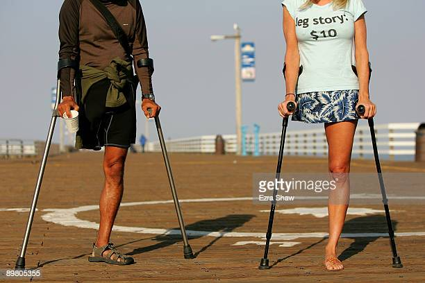 Amputee surfers Mario Rodriguez and Julie Carruthers aka OneLeggedJoe stand on the pier before participating in Operation Restoration IV on August 14...