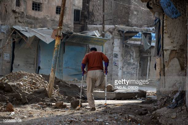 TOPSHOT A amputee uses crutches to walk in a debrisstrewn street in the old neighbourhood of the northern Iraqi city of Mosul on November 7 2018...