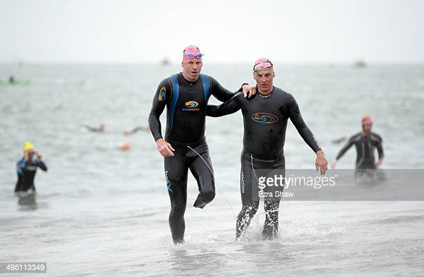 Amputee William Nystrom is helped out of the water by Brian Cowie during the 2014 Escape from Alcatraz Triathlon on June 1 2014 in San Francisco...