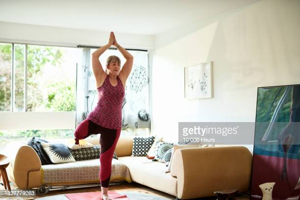 amputee woman balances in yoga position at home - greater london stock pictures, royalty-free photos & images