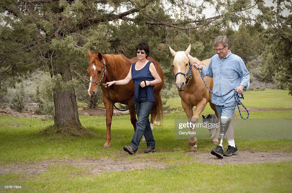 Amputee w/wife, leading horses down a path : Stock Photo