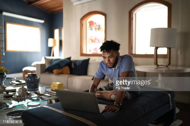 amputee young man watching movie on a laptop at home - disabilitycollection stock pictures, royalty-free photos & images