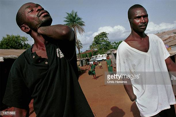 Amputees missing arms and ears walk around June 5, 2001 in a camp for amputees in Freetown, Sierra Leone. The prospects for peace in Sierra Leone are...