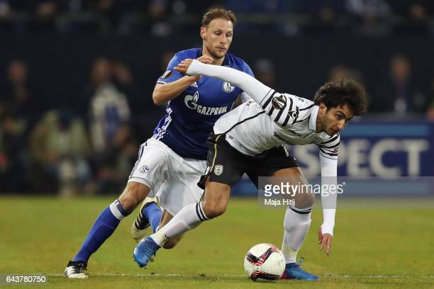 Amr Warda of PAOK is challenged by Benedikt Hoewedes of Schalke during the UEFA Europa League Round of 32 second leg match between FC Schalke 04 and...