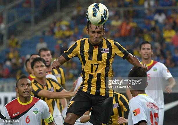 Amri Yahyah of Malaysia heads the ball against East Timor players during their 2018 World Cup qualifying Group A match in Kuala Lumpur on June 11...