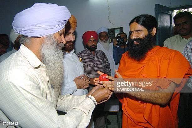 An Indian prisoner presents a flower to Yoga Guru Swami Ramdev as he arrives at The Central Jail in Amritsar17 November 2006 Hundreds of prisoners...