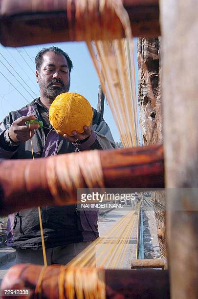 An Indian worker rolls kite threads on a road side in Amritsar in India's northwestern state of Punjab 07 January 2007 Demand for kites is rising...