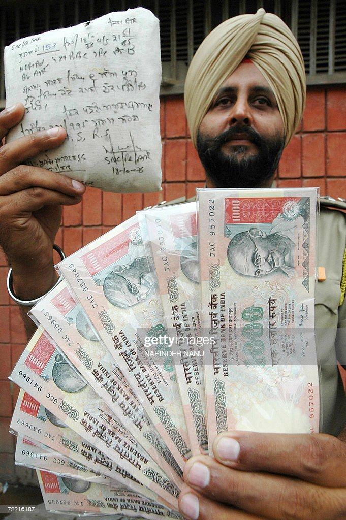 An official from India`s Special Narcotics Cell of India`s Punjab police force poses with a sheaf of fake one thousand Indian Rupee notes and a...