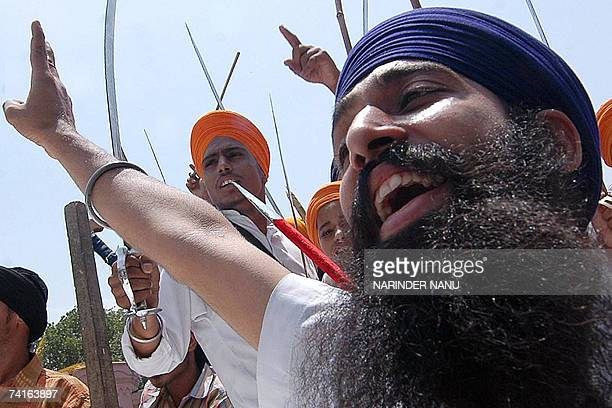 Indian activists of radical Sikh organisations brandish swords as they hold a protest against the chief of the spiritual organisation Dera Sacha...