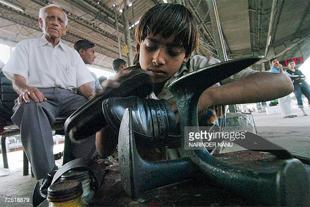 Indian child Vishal polishes shoes at the Amritsar Railway Station 13 November 2006 on the eve of 'children's day' Despite a ban on children's labour...