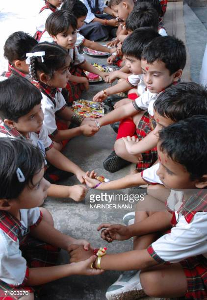 Indian children ties 'rakhi' on each other's wrists on the eve of the Hindu festival Raksha Bandhan in a school in Amritsar 08 August 2006 The annual...