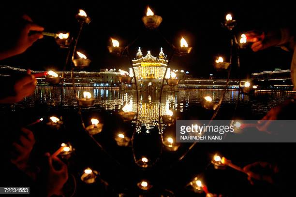 Indian devotees light candles in the forefront of the illuminated Golden temple in Amritsar on the occasion of Bandi Chhor Divas in Amritsar 21...