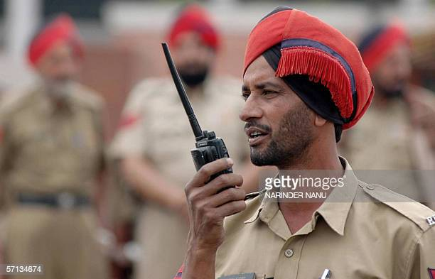 Indian policemen from the Punjab Police Force stand alert during a security procedure at The Golden Temple Complex in Amritsar 20 March 2006 in...