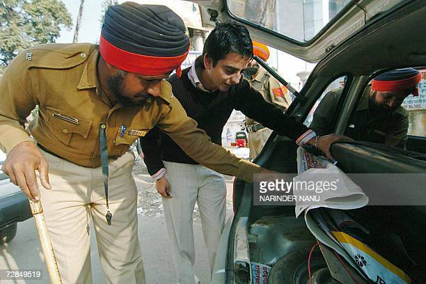 Indian Punjab policemen check a motorcar during a security check in Amritsar 19 December 2006 Security has been beefed up prior to the visit of the...