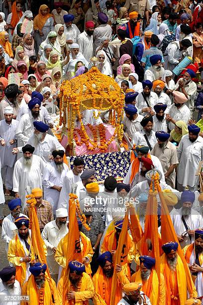 Indian Sikh devotees carry the Palki Sahib as they take part in a procession in Amritsar 01 May 2006 on the eve of the 443rd birth anniversary of the...
