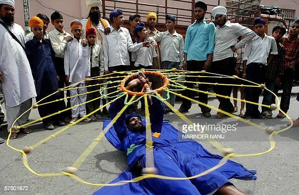 Indian Sikh devotees look on as a Nihang performs Gatka a Sikh martial artas he takes part in a procession in Amritsar 01 May 2006 on the eve of the...