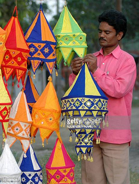 Indian street vendor Raju Bhat adjusts his display of cloth lampshades at his roadside stall in Amritsar 14 October 2006 ahead of the Diwali Festival...