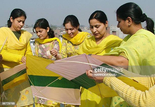 Indian women clothed in yellow prepare to fly kites on the occassion of Basant Panchami the Festival of Spring in Amritsar 02 February 2006...