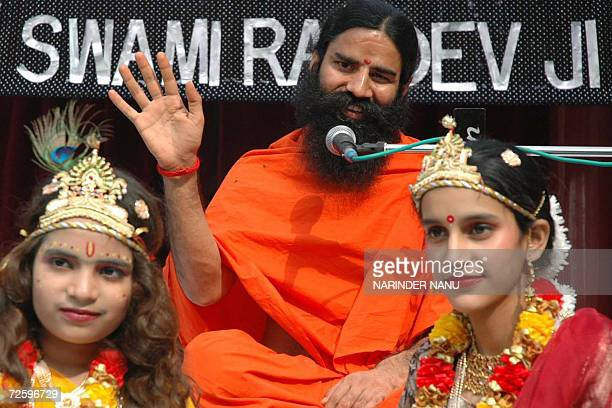 Indian Yoga Guru Swami Ramdev gestures as he sits with children dressed as Hindu Gods Krishna and Radha during his visit to a school in Amritsar 18...