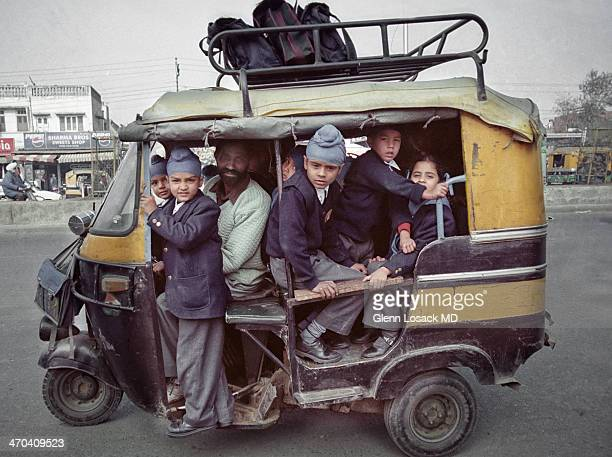 CONTENT] Amritsar INDIA school children in a tuc tuc which is basically motorcycle based a small vehicle most common form of transport in INDIA