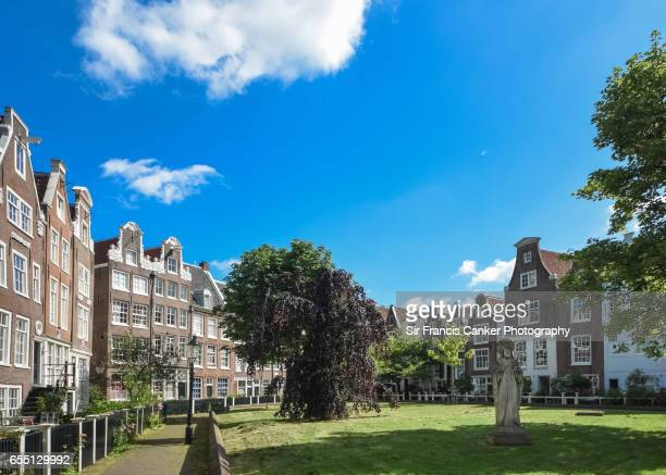 Amsterdam beguinage, a beautiful courtyard surrounded with 17th and 18th century houses in old town Amsterdam, the Netherlands