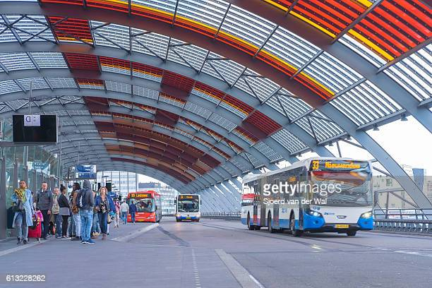 "amsterdam bus station with people boarding the busses - ""sjoerd van der wal"" stockfoto's en -beelden"
