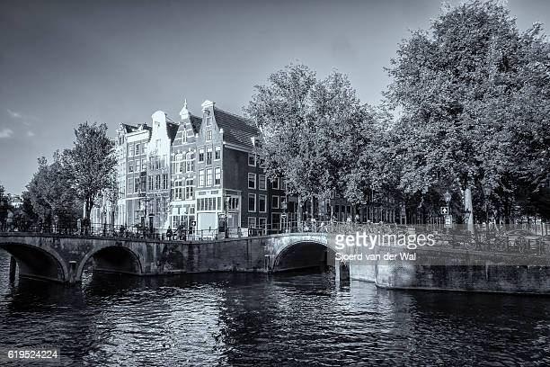 "amsterdam canal and traditional houses in early autumn - ""sjoerd van der wal"" stockfoto's en -beelden"