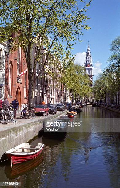 Amsterdam canal with boats on the water and people walking