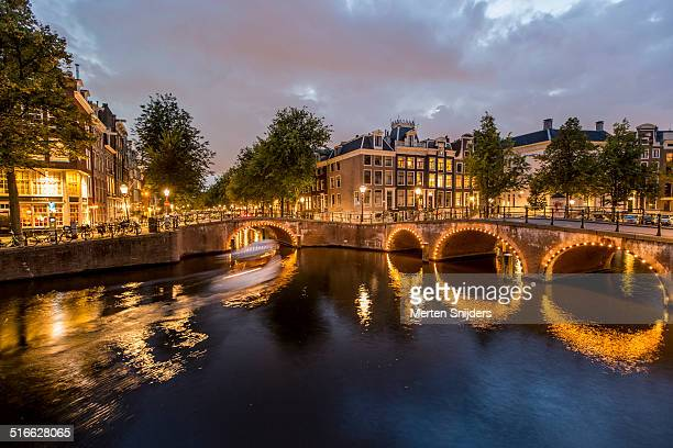 amsterdam canal with lit bridge on keizersgracht - merten snijders stock pictures, royalty-free photos & images