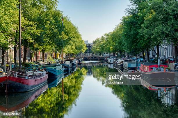 amsterdam canal with the boat houses and reflections - amsterdam stock pictures, royalty-free photos & images