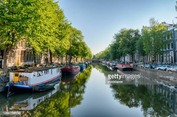 amsterdam canal with the boat houses and reflections - canal stock pictures, royalty-free photos & images